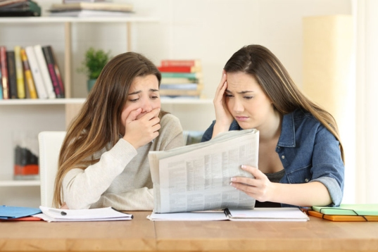 women looking at print student newspaper